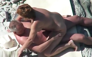 Mature nudist couple caught fucking to hand the seaside
